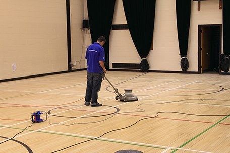 Man using floor sander on a gym floor in London