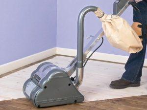 Drum sander in use on half sanded hardwood floor
