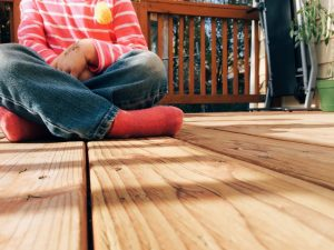 child sat on sanded wooden deck