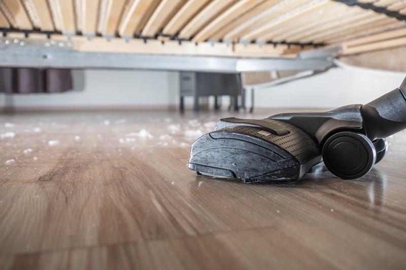 hoovering dust off wooden floor