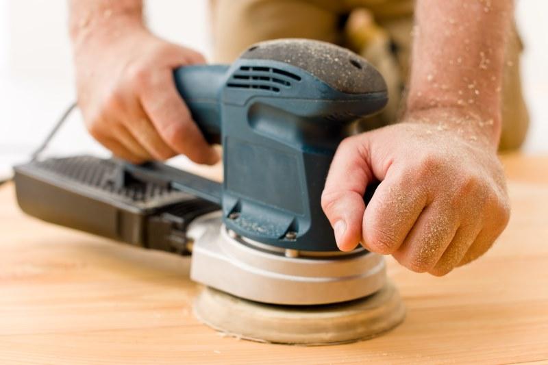 man sanding wooden floor in workshop