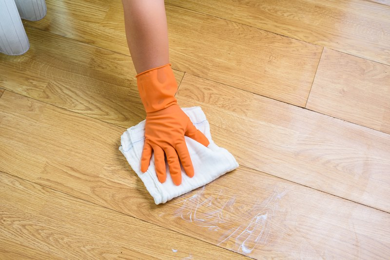 Hand in gloves cleaning Wooden floor with rag and cleanser at home. housework and housekeeping concept
