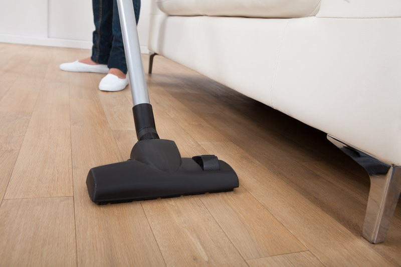 Low section of woman vacuuming hardwood floor at home