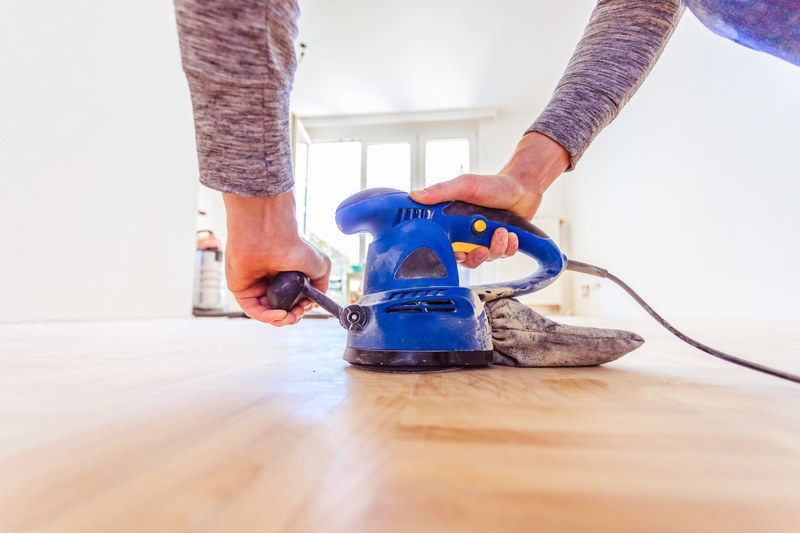 man sanding his wooden floor